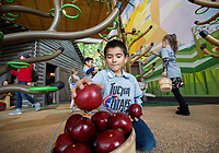 NWA Democrat-Gazette/JASON IVESTER<br /> Jaden Pina, Tucker Elementary kindergartener, collects apples in the Homestead Cabin and Farm exhibit Thursday, March 16, 2017, at the Scott Family Amazeum in Bentonville. About 100 students from the five kindergarten classes at the Rogers school were on a field trip at the museum.