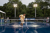 Tournament worker Tim Stout cleans off the court following a thunderstorm during the Legg Mason Tennis Classic at the William H.G. FitzGerald Tennis Center in Washington, DC.