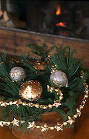 A Christmas decoration on a table beside the fire in the living room