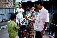 (L-R) Shakil Alom (7, son), Mohd. Abu Taleb (41, husband), Mahfuza Akhter (5, daughter), Shahida Begum (35), Akhterruzzaman (38, Hub Manager). .Shahida Begum, 35, meets her Hub Manager, Akhterruzzaman, in her hut's compound in Palashbari Villlage, Taragonj, Rangpur, Bangladesh on 18th September 2011, after a regular day of work as a saleswoman, earning 3500 - 5000 Bangladeshi Taka per month. She is one of many rural Bangladeshi women trained by NGO CARE Bangladesh as part of their project on empowering women in this traditionally patriarchal society. Named 'Aparajitas', which means 'women who never accept defeat', these women are trained to sell products in their villages and others around them from door-to-door, bringing global products from brands such as BATA, Unilever and GDFL to the most remote of villages, and bringing social and financial empowerment to themselves.  Photo by Suzanne Lee for The Guardian