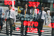 Japanese business men, known as salarymen, are reflected in a bank stocks and shares monitor screen, showing the latest values of commodities, in Marunouchi district, Tokyo, Japan.