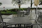 Rain droplets on metal tables and chairs against the background of Lake Bodensee and couple with umbrella. Birnau, Lake Bodensee, Bavaria, Germany. rain,wet weather,landscape,café table,puddle reflection,puddles,water, rainfall,damp weather,