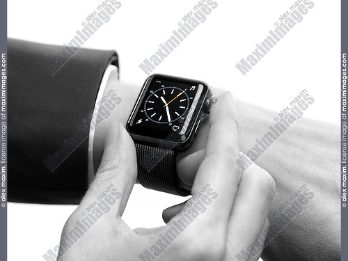 Woman hand with Apple Watch smartwatch on her wrist displaying a clock dial isolated on white background