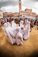 A group of nuns are walking around the Piazza del campo before the start of the parade, one of them seem to be an expert and is explaining the others about the Palio