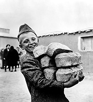 Polish youngster with his arms loaded down with bread made from flour supplied by the American Red Cross.  Smile is in anticipation of enough bread to eat, something he would not get if he had stayed in his native Poland, Russia, ca. 1943. OWI.  (Army)<br /> Exact Date Shot Unknown<br /> NARA FILE #:  111-SC-170234<br /> WAR &amp; CONFLICT BOOK #:  1256