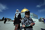 A Palestinian boy dressed as a soldier plays in front of the Dome of the Rock mosque following Friday prayers at the Al-Aqsa compound, Islam's third holiest site, in the old city of Jerusalem January 31, 2014. Photo by Saeed Qaq