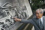 Sunao Tsuboi points to himself in a photograph by  Yoshito Matsushige, taken on Miyuki Bridge 3 hours after the atomic bombing of Hiroshima. This was the first photo taken after the bombing, and shows Sunao Tsuboi sitting injured on the bridge. Hiroshima, Japan, 21.07.2005