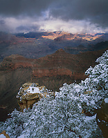 Grand Canyon National Park, AZ   <br /> Sunset light breaks through clearing winter storm clouds to illuminate canyon from Mather Point at the South Rim