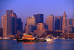 Tugboat in Boston Harbor glides by the Boston skyline at sunrise.