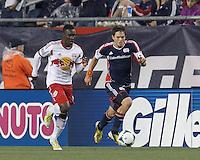 New England Revolution midfielder Kelyn Rowe (11) brings the ball forward as New York Red Bulls midfielder Lloyd Sam (10) closes. In a Major League Soccer (MLS) match, the New England Revolution (blue) tied New York Red Bulls (white), 1-1, at Gillette Stadium on May 11, 2013.