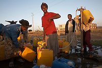 Filling water containers at a water disturbution point on the road to Nazret in the rift valley of Ethiopia. Much of the daily lives of the people here are taken up by the burden of water collection.