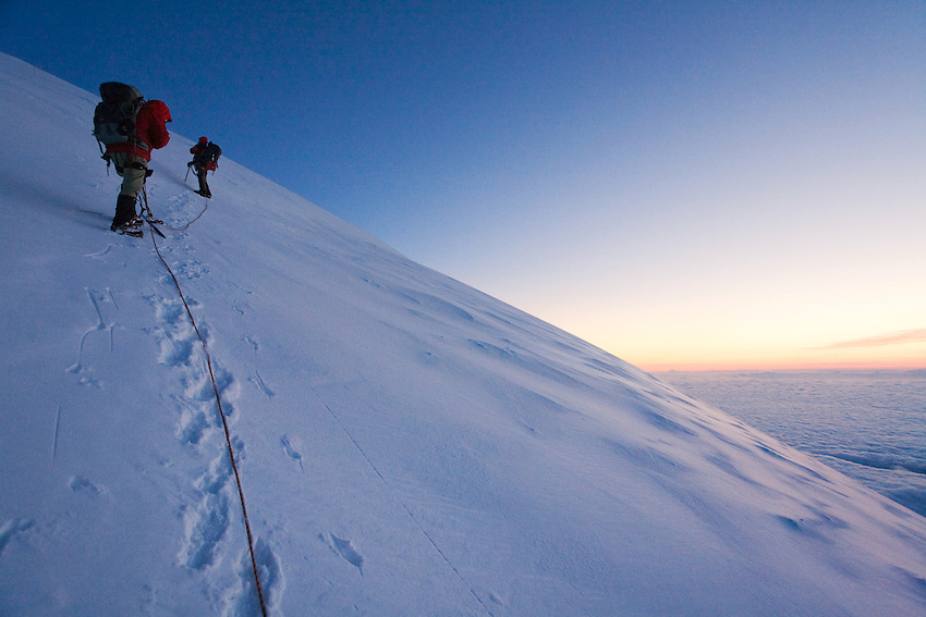 """""""RAINIER DAWN"""" -- Roped mountain climbers ascend the upper slopes of Washington State's Mount Rainier. During a break at nearly 14,000 feet, the climbers enjoy a beautiful sunrise."""