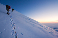 &quot;RAINIER DAWN&quot; -- Roped mountain climbers ascend the upper slopes of Washington State's Mount Rainier. During a break at nearly 14,000 feet, the climbers enjoy a beautiful sunrise.
