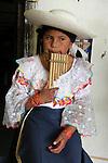 South America, Ecuador, Peguche. A young Ecuadorian girl plays the panflute, a traditonal instrument of the Andes.