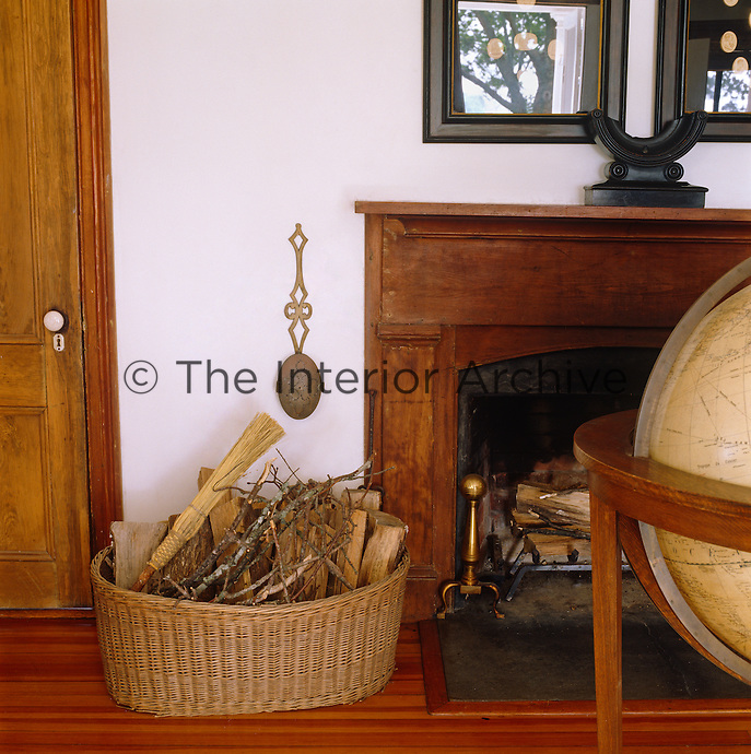 Detail of the fireplace with a log basket and old fashioned French globe