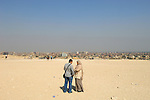 Couple in discussions on the desert hills which seperate the Pyramids at Giza from the city.