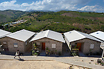 """Some houses in a model resettlement village constructed by the Lutheran World Federation in Gressier, Haiti. The settlement houses 150 families who were left homeless by the 2010 earthquake, and represents an intentional effort to """"build back better,"""" creating a sustainable and democratic community."""