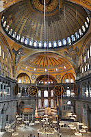 High angle view of interior and domes showing Islamic elements in the ceiling, and the mirhab below, Hagia Sophia, 532-37, by Isidore of Miletus and Anthemius of Tralles, Istanbul, Turkey. Hagia Sophia, The Church of the Holy Wisdom, has been a  Byzantine church and an Ottoman mosque and is now a museum. The current building, the third on the site, commissioned by Emperor Justinian I, is a very fine example of Byzantine architecture. The historical areas of the city were declared a UNESCO World Heritage Site in 1985. Picture by Manuel Cohen.