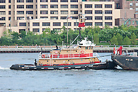 Tugboat Franklin Reinauer pushing a barge on the East River past Brooklyn Bridge Park