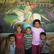 Roma children stand in front of a scene from a Persian story painted on the wall of a home, in the old part of the Sintesti Roma camp.  These Arabian scenes are very popular as wall decoration, but no-one within the camp knows the reason why they were first painted.