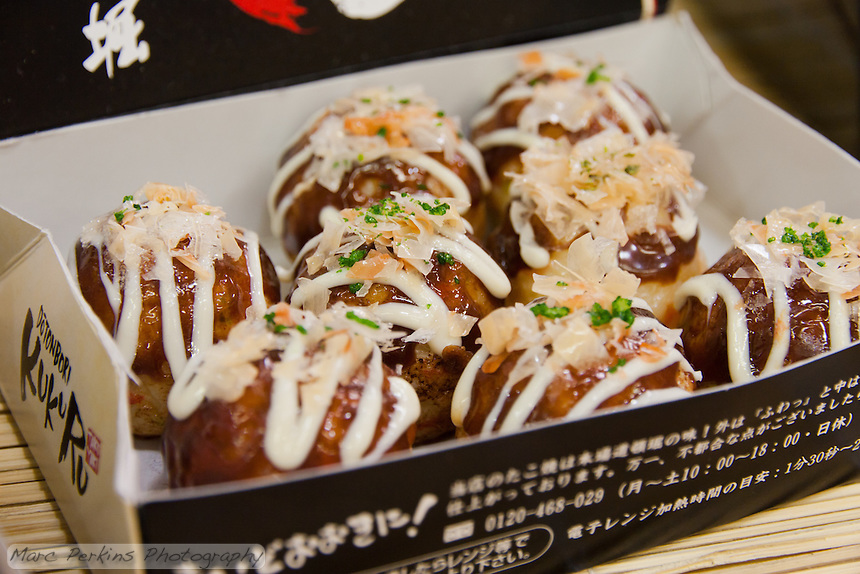 Eight complete takoyaki on display  during a demonstration of takoyaki cooking at Mitsuwa Market in Costa Mesa, California.  As is common in Japanese restaurants, the samples on display are actually just exceptionally well made models.  But these show off what takoyaki are much better than the real thing.