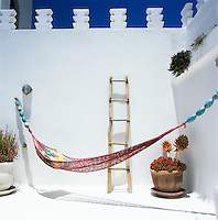 A hammock hangs in a corner of the whitewashed roof terrace of this Moroccan house