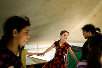 A group of girls hold hands and dance in a circle in a tent at the Zaatari Refugee Camp. Approximately two million people have fled the conflict in Syria. At least 130,000 of them live in Zaatari Refugee Camp, although it was designed to house 60,000, and a further 2,000 people arrive each day.