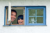 Newlyweds Claudia and Daniel greet their guests through a small window during their wedding reception in Seattle. (Photo by Dan DeLong/Red Box Pictures)