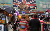 """Open air areas with stalls and customers, Candem Town markets, open-air and indoor markets, London, UK. The wall poster showing a lion with the Union Jack is the emblematic picture of """"Camden World Famous Market"""". Picture by Manuel Cohen"""