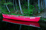 Red canoe floats as if on glass during the Evening calm on Robinson Lake, North Idaho