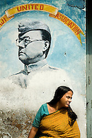"A woman in kolkata sits in front of a wall painting of Subhas Chandra Bose. He was one of the most prominent leaders in the Indian independence movement and led military forces against Britain and the Western powers during WWII. He died in 1945, and remains a legendary figure in India. Netaji means ""Respected Leader."""