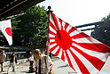 August 15, 2011 - Tokyo, Japan - A man holding up the flag of Japan bows before entering Yasukuni Shrine. Thousands of people visit this shrine to pay their respect to the Japanese war soldiers who died fighting in World War II which marks the 66th anniversary of the end of WWII. (Photo by Christopher Jue/AFLO)