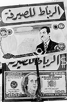 Iraq. Baghdad. Banknotes of iraqi dinar with Saddam Hussein and a hundred american dollar with Franklin Roosevelt are drawn on an outside advertising for a money changer's shop in the street. © 2003 Didier Ruef