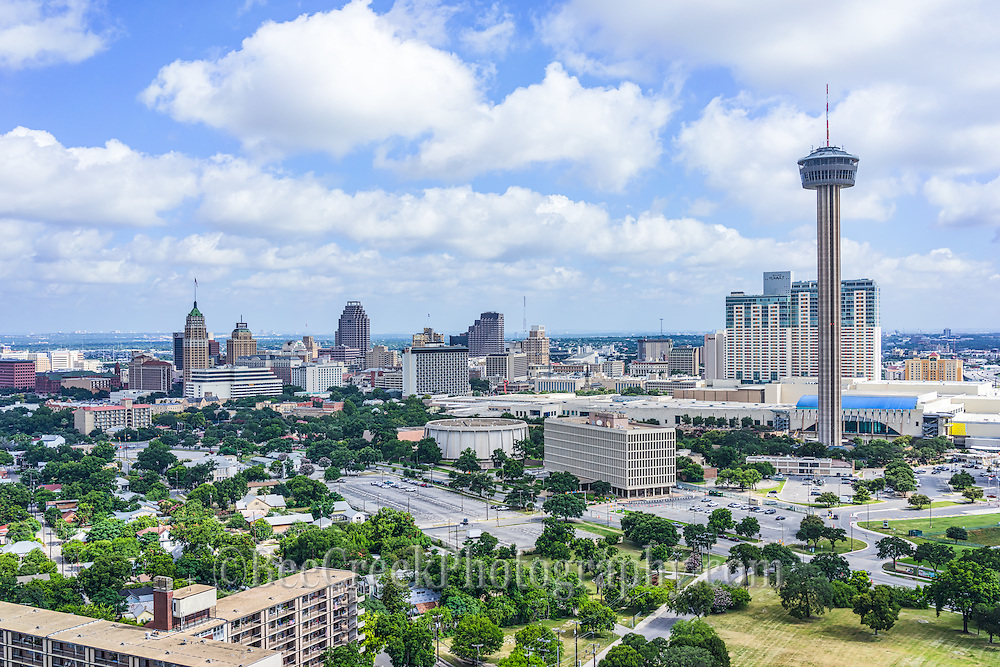 This is aerial of another angle of the city of San Antonio with the tallest building in Texas the Towers of Americas, also called the Hemisphere, the  Henry B Gonzales Convention Center, Weston Center, Grand Hyatt, and other iconic buildings like the Tower Life Building, Weston, Marriott, Bank of America Center, and many hotels that  run along the River Walk in the city.