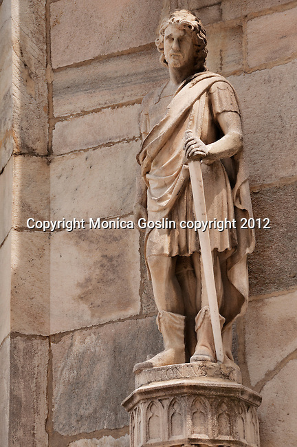 Statue on Duomo in Milan, Italy which is covered in sculptures and carved stone details