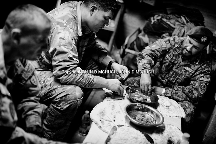 US Army Captain Michael Brabner (C), Charlie Company Commander, 2/27 Infantry, 25th Infantry Division, and his Sergeant Major, Royce Manis (L), is seen eating with Afghan National Army Colonel Hallimshah Qudri at Observation Post Mace, near Gowerdesh in northern Kunar, 20 November 2011. (John D McHugh)