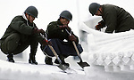 Japanese Self Defense Force snow sculptures uses shovel snow from an ice sculpture in Odori Park. These are not traditional Frosty the Snowmen, but huge carved and chiseled Samurai Warriors, Buddhists gods, historical heroes of fairy tales and Walt Disney characters. Some stand as big as buildings. Chiseled out of tons of packed snow, the sculptures are the pride and job of the residents of Sapporo, Japan, who hosts the world famous Ice and Snow Sculpture Festival for five days in early February.Themes of the sculptures are picked from Kabuki stages, historical characters or fairy tales. (Jim Bryant Photo).....