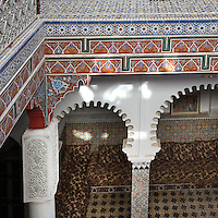 Pillars and fluted horseshoe arches around the central courtyard with zellige tile decoration and painted wooden panels, in a typical Tetouan riad, a traditional muslim house built around a courtyard, built in Moorish style with strong Andalusian influences, next to the Great Mosque or Jamaa el Kebir in the Medina or old town of Tetouan, on the slopes of Jbel Dersa in the Rif mountains of Northern Morocco. Tetouan was of particular importance in the Islamic period from the 8th century, when it served as the main point of contact between Morocco and Andalusia. After the Reconquest, the town was rebuilt by Andalusian refugees who had been expelled by the Spanish. The medina of Tetouan dates to the 16th century and was declared a UNESCO World Heritage Site in 1997. Picture by Manuel Cohen
