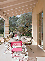 A dining area on the covered terrace with a mixture of pink and taupe folding chairs