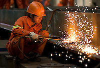 A worker welds steel in the workshops of a factory on Changxing Island, near Shanghai, on October 13, 2008. Baosteel, China's biggest steel producer, is to take over Ningbo Iron and Steel Group and Baotou Iron and Steel Group. The Chinese government is encouraging mergers in order to restructure the steel industry, according to the steel industry stimulus plan approved by the State Council in January. Photo by Servais Mont/Pictobank