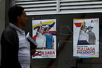 BOGOTA, Colombia. 13th June 2014. A man walks next to posters of presidential candidate Oscar Ivan Zuluaga and Alvaro Uribe in Bogota few days before presidential election in Colombia. Photo by Eduardo Munoz Alvarez/VIEWpress