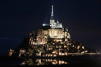 Clinging to the north flank of the rock, Gothic monastery known as the Merveille (Marvel) by night, Le Mont Saint Michel, Manche, Basse Normandie, France. Two three-storey buildings, crowned by the cloister and the refectory, fifty meters high, beginning of the 13th century thanks to a donation by the king of France, Philip Augustus who offered Abbot Jourdain, a grant for the construction of a new Gothic-style architectural set. Picture by Manuel Cohen