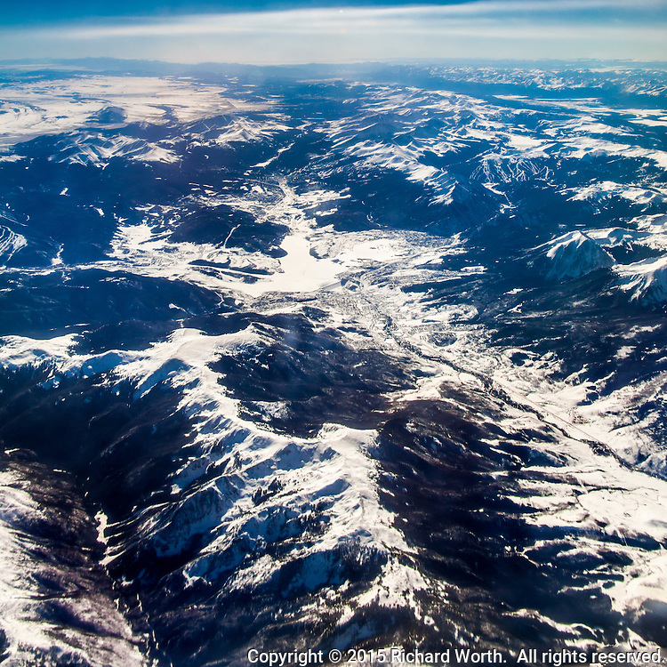 A high altitude aerial view of the Rocky Mountians through the window of a commercial passenger plane flying  from Colorado to California in winter.