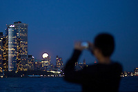 A full moon rises over the skyline of New York , April 25, 2013. by Eduardo Munoz / VIEWpress