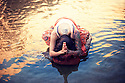 Anonymous woman in a devotional namaste yoga posture in the water.