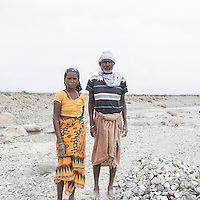 India – West Bengal: Shoma (right) and Sugi Munda, respectively 56 and 45, posing while crushing pebbles and stones along the Diana riverbed at Red Bank Tea Estate, in the Dooars region. The garden, which houses 888 workers out of a population of 5,000 people, has been closed since 2013. With no more income, food rations and health services, its workers resorted to stonecrushing in order to survive. According to Shoma, the tea estate started to get into troubles in 1993. The company first stopped mending the workers' houses, then, few months later, it closed down. Then, a series of different owners took over, each of them reopening the gardens for a few years of months, before disappearing again. Workers were not paid any arrear.