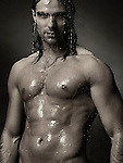 Dramatic portrait of a young man with wet bare torso standing under a shower with water running down his body. Black and white sepia toned;