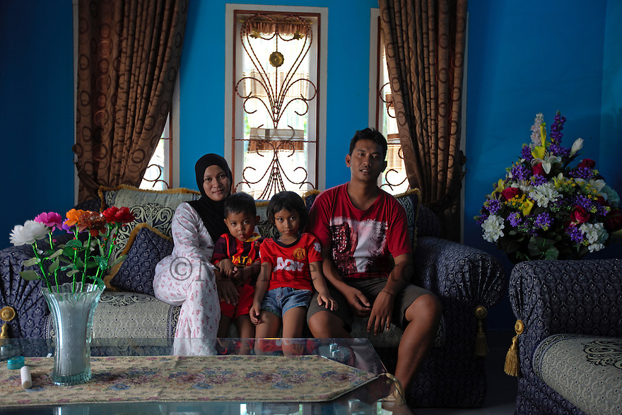 Indonesia - Bangka Island - Pemali - Asram Somat, 30 sitting in the living room of his house next to his wife Linda, 29 and his children Nabila, 7 and Irfan 4. His house is attached to his workshop, where his workers process and dry the tin, before selling it to the independent smelters. A friendly 30-year-old man from the village of Pemali and father of two kids, Somat is one of the several middlemen buying tin from illegal miners through an array of private collectors. Somat processes and sells around three tons of tin concentrate per week to some of the independent smelters, at an average price of 16 USD per kilo. While his business is regularly licenced, Somat pays 1,000,000 IDR (around 100 USD) per month to the police to avoid problems.