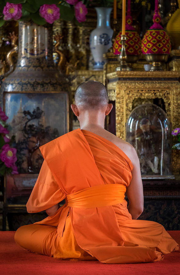 BANGKOK, THAILAND - CIRCA SEPTEMBER 2014: Buddhist monk praying inside the Ordination Hall in Wat Arun, a  popular Buddhist temple in Bangkok Yai district of Bangkok, Thailand, on the Thonburi west bank of the Chao Phraya River
