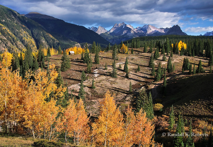 A lonely cabin stands on a hillside surrounded by conifers and aspen, San Juan National Forest, Colorado. The Grenadier Range looms in the background.
